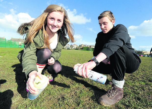 The Wiltshire Gazette and Herald: Year 10 students Jenna and Ollie get ready to spray a 'crop circle' design in the shape of a Dyson Airblade drier.        (DV1138) By diane vose