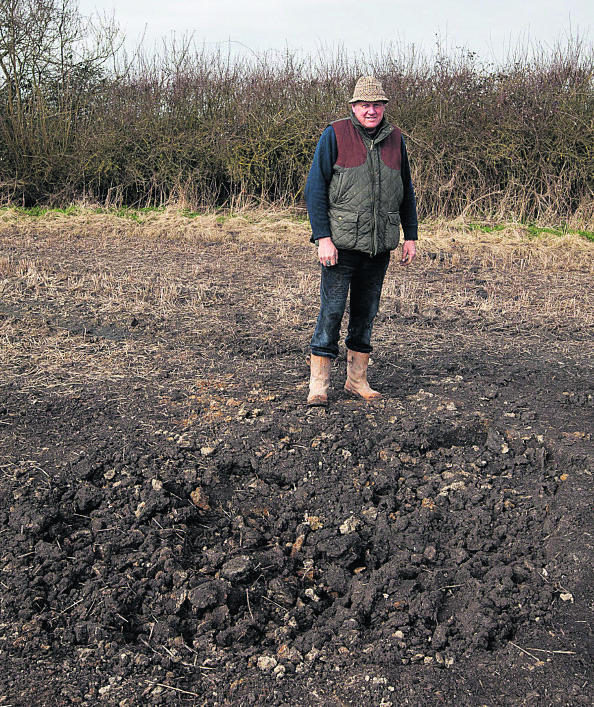 Andrew Snook next to the crater on his farm at Patney. An Army shell landed in