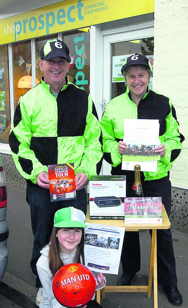 The Wiltshire Gazette and Herald: Pete and Carol Parsons with daughter Hannah and some of the prizes for the race night in the Bouverie Hall, Pewsey, on Saturday, March 29