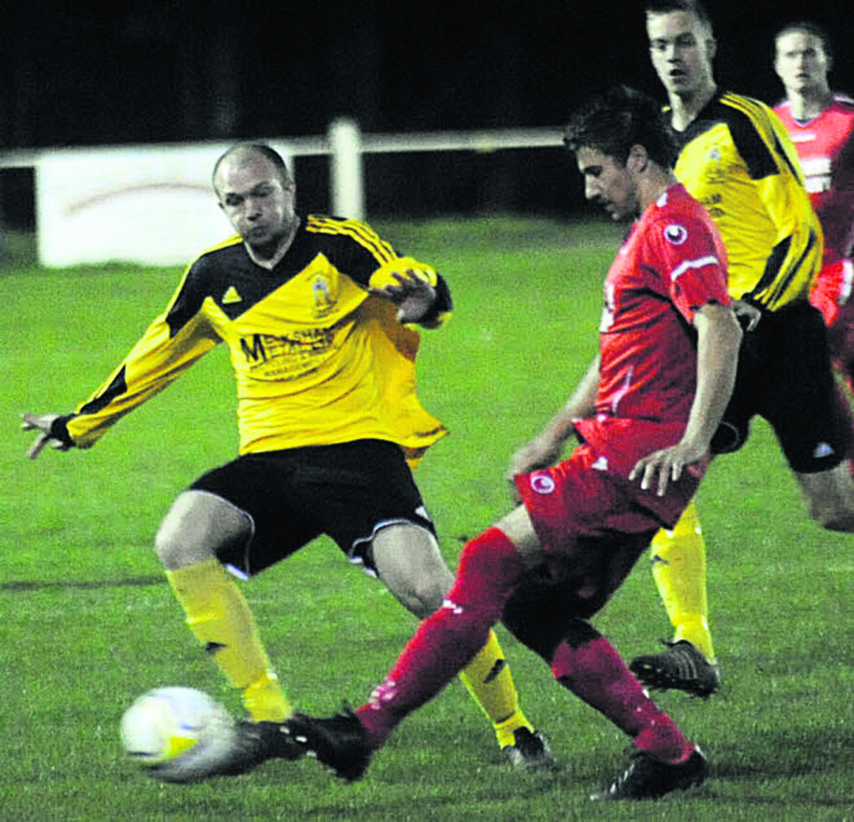 Melksham Town's Shaun Benison (yellow) challenges Jamie Richards, of Purton, in Tuesday night's Wiltshire Senior Cup semi-final