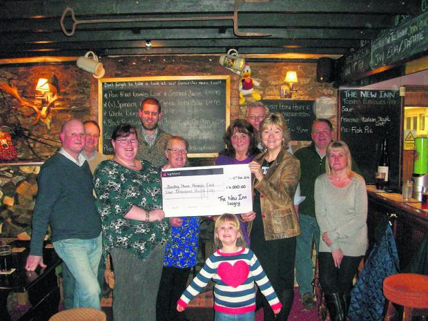 Upper Seagry fundraisers with their cheque for £4,000: Toddy Park, George Candy, Sarah and Karl Adkins, Helen Greenhill, Viv Read, John Greenhill, Yvonne Brunton  from Dorothy House, John Branston, Lorraine Drummond and, front, Grace Adkins