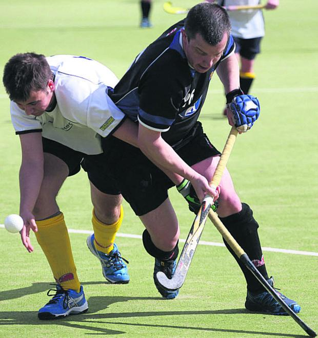 The Wiltshire Gazette and Herald: Devizes' Roger Edwards (black) battles with Team Bath Buccaneers 4th's Will Mainwaring during Saturday's 5-3 win, which wrapped up promotion