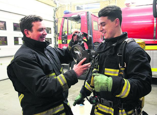 Firefighter Stuart Hillier shows Zac Messenger how to use breathing apparatus