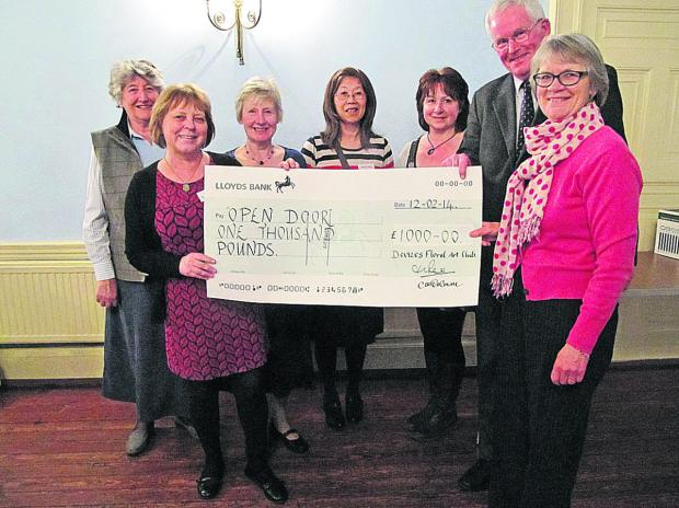 Devizes Floral Art Club vice-chairman Di Remlinger hands a cheque of £1,000 to its charity of the year Open Door