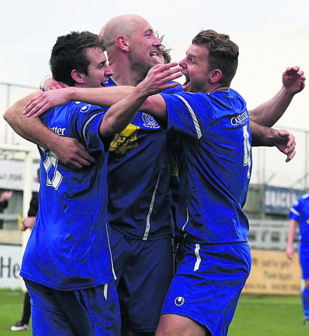 The Wiltshire Gazette and Herald: Goalscorer James Guthrie (left) takes the congratulations of Alan Griffin and Bryan Smith after putting Chippenham Town 2-0 up against Banbury United last weekend