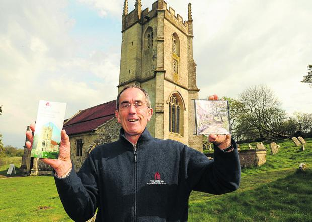 Neil Skelton at St Giles Church with the CD the Ghosts of Old Imber       (TP48664) By Trevor Porter