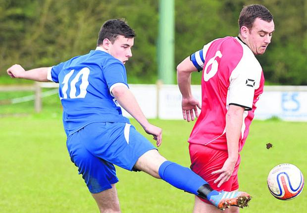 The Wiltshire Gazette and Herald: Corsham's Ben Moore battles with Ryan Rawlins, of Devizes, during Monday's derby