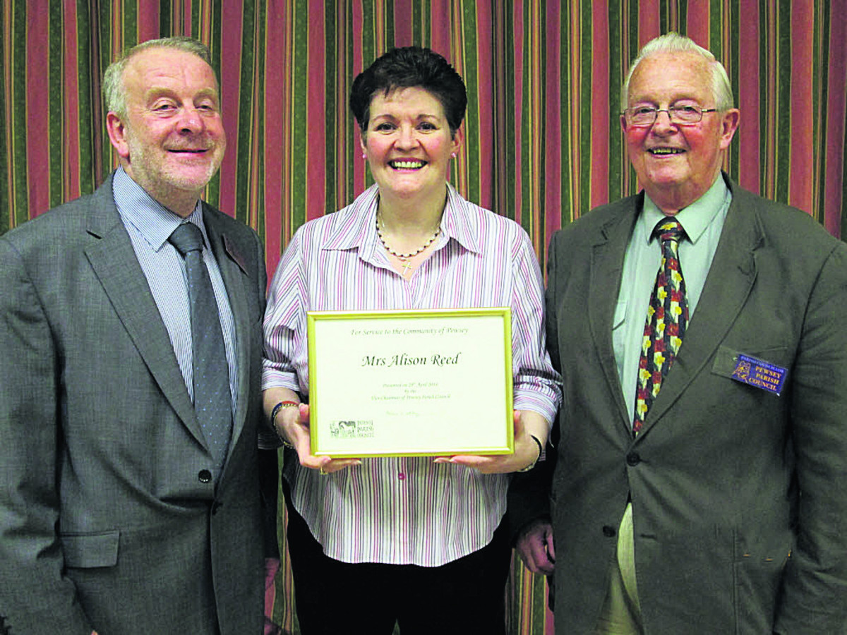 Andrew Whitney, present chairman of Pewsey Parish Council, and Alex Carder, previous  chairman, present a community service award to Alison Reed