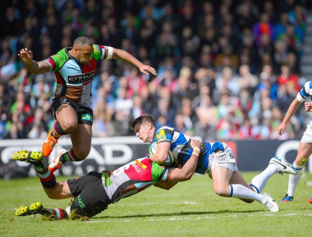 Bath Rugby's Ollie Devoto (right) is tackled by Harlequins' Maurie Fa'asavalu