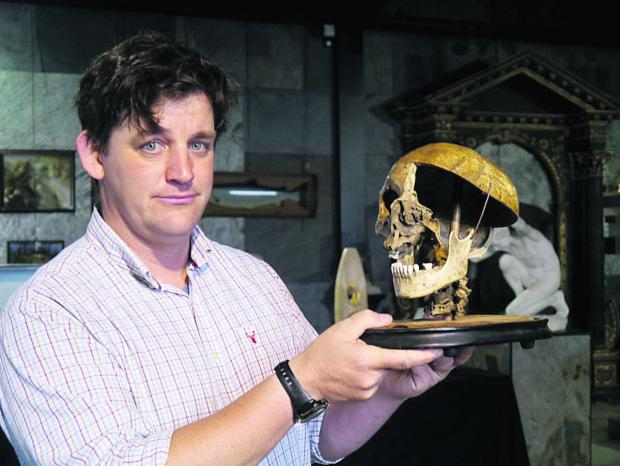 Specialist Rupert van der Werff with the felon's skull going under the hammer in Tuesday's natural history auction