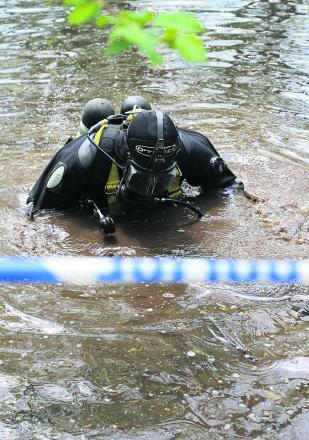 A police diver searches the pond at Ramsbury