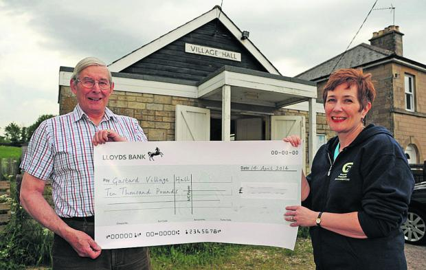Gastard Village Hall secretary John Varley and treasurer Debbie Anstis with one of the cheques that topped their £20,000 target                                                       (TP48821) By Trevor Porter