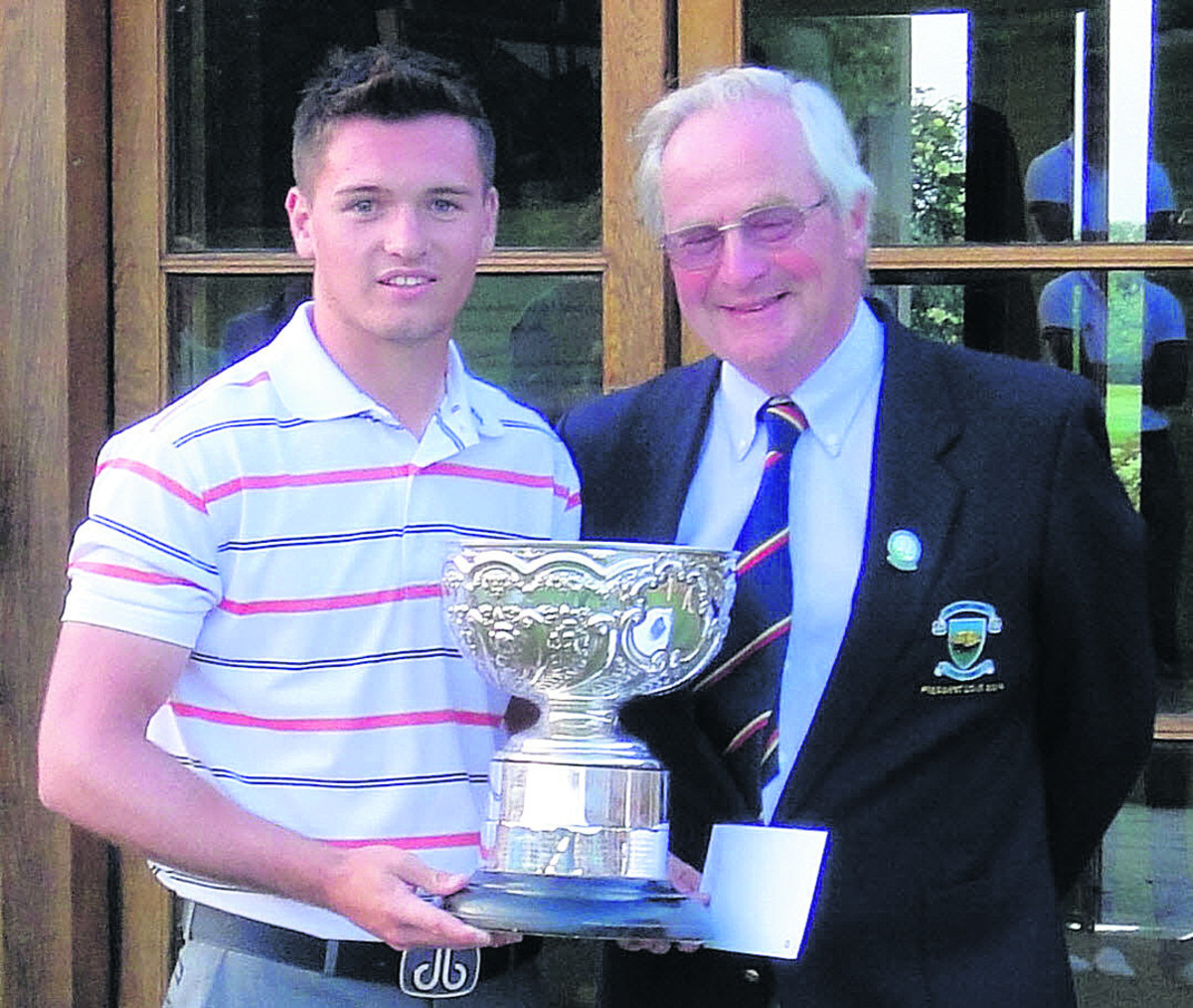 Ben Amor receives the County Championship trophy from Wiltshire Golf Union president, Barrie Reardon Smith