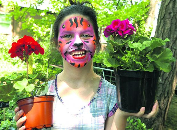 Zara Walker has her face painted to match the plants at Rowdeford Garden Fair
