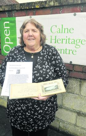 Sue Boddington with a Calne woman's lodging book filled with signatures of trainee pilots from Yatesbury Camp
