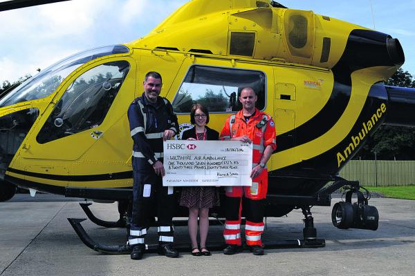 Haine & Smith marketing manager Rachel Wheeler reveals the final amount raised with help from police observer PC Nigel Gilbert and air ambulance paramedic Matt Baskerville