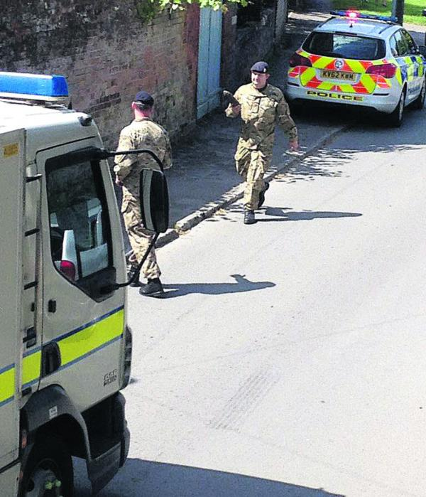 Bomb disposal officers remove the spent artillery shell from Urchfont yesterday