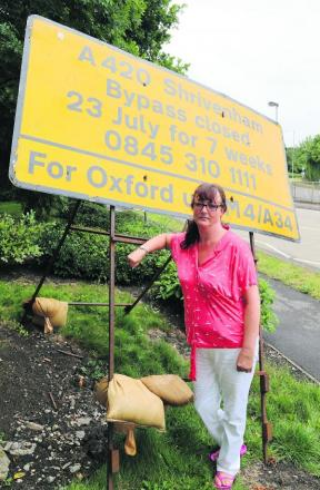 Shrivenham Parish councillor Sarah Day pictured at a sign warning drivers about the closure of the A420 between Swindon and Oxford for seven weeks starting tomorrow