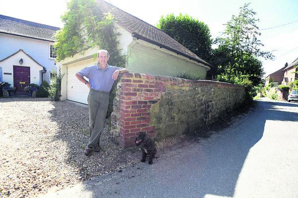 Peregrine Rawlins next to his damaged wall, which he has had to repair after it was struck by lorries              (DV1458) By Diane Vose