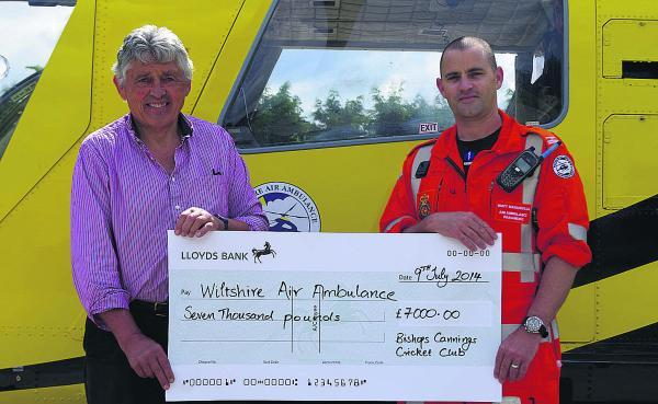 Ed Davies, chairman of Bishops Cannings Cricket Club, presents the cheque to Matt Baskerville, paramedic at Wiltshire Air Ambulance