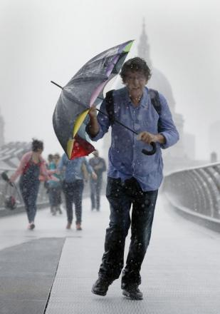 A pedestrian stuggles against the wind and rain in London today
