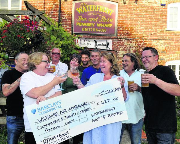 Volunteer Tracey Pullen, front left, receives the cheque from co-owners Nicky Rouse, Nigel Wallace and chef Carl Games. Other fundraisers are, from back left, Frank Day, Richard Stawt, Liz Boden, Wayne Richards and Nick Clark      (SMB050/1) By Siobhan Bo