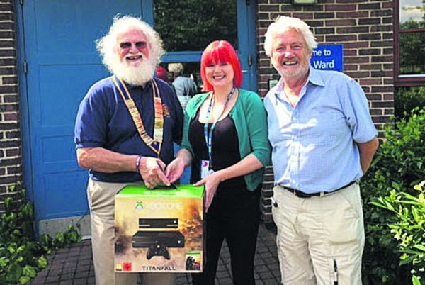 Devizes Rotary Club president Tom MacMeekin, left, and past president Geoff Collins present the Xbox to Green Lane Hospital ward manager Hannah MacDonald