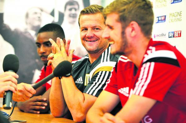 Mark Cooper, flanked by his signings Jonathan Obika (left) and Jack Stephens, is a happy man