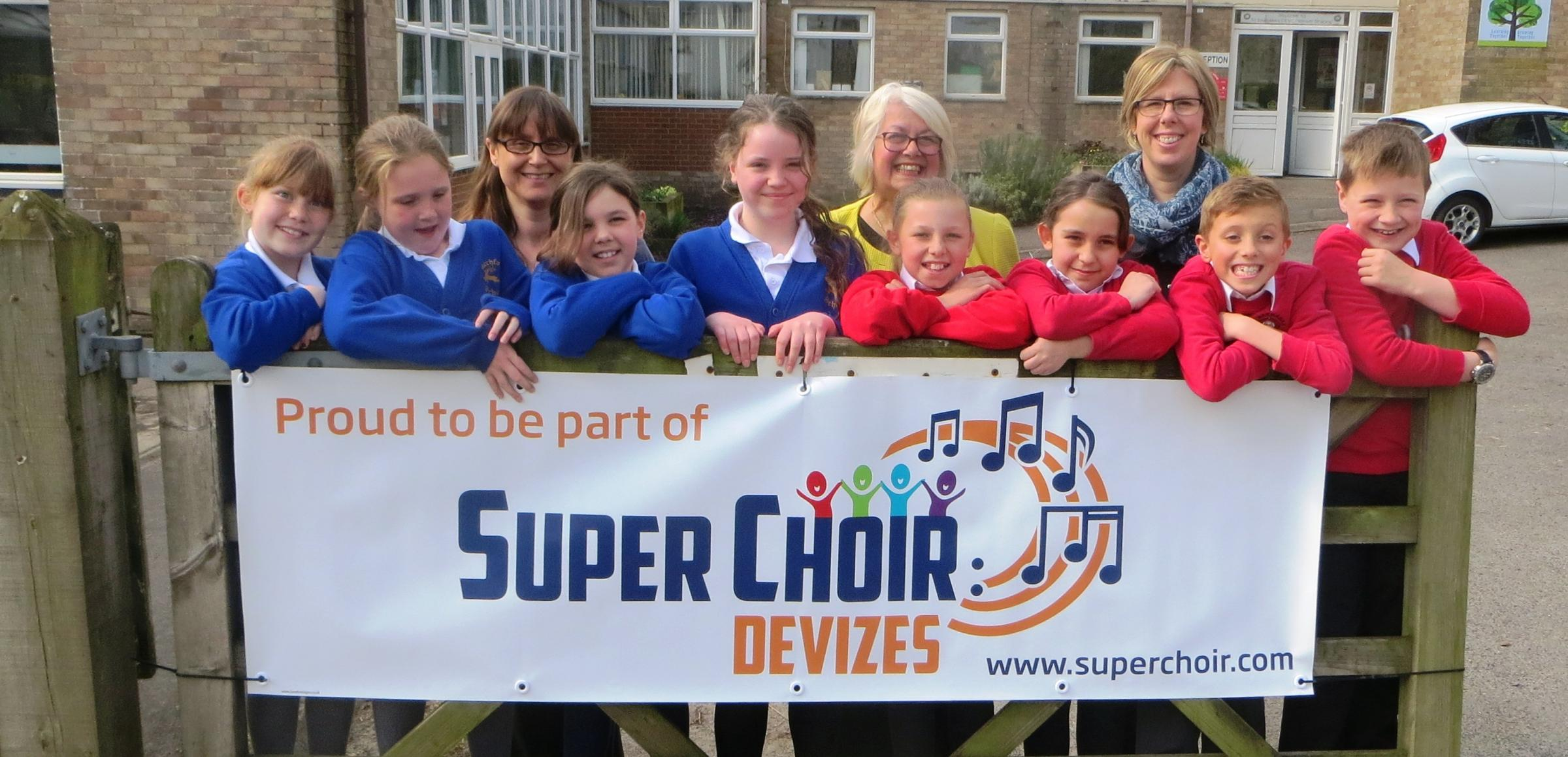 Pictured at St Barnabas school in Market Lavington unveiling their banner this week are (back row L to R) Fiona Underwood from Urchfont C of E Primary School, Carole Berry SuperChoir Artistic Director and Lindsay Clough from St Barnabas C of E Primary.