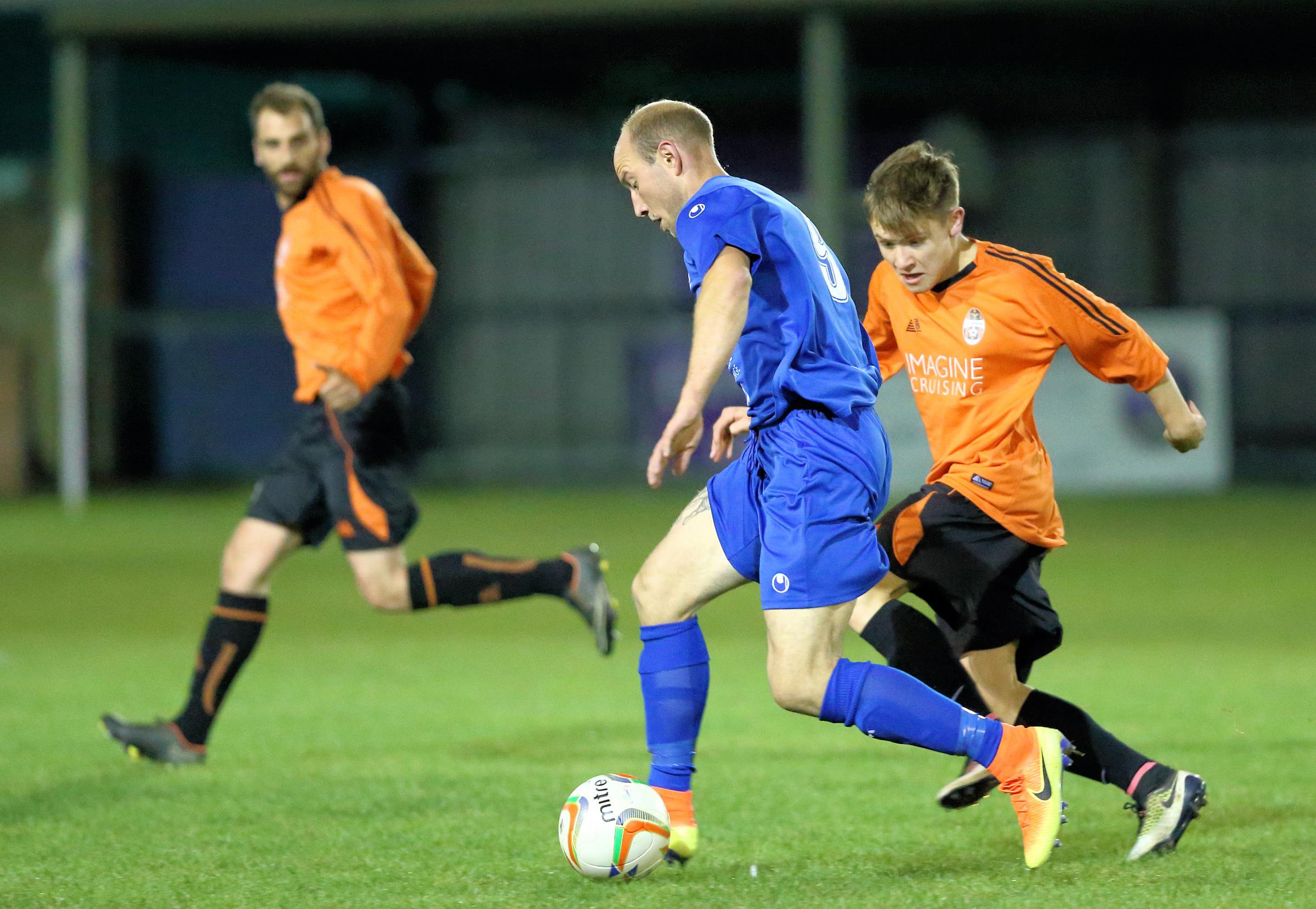 Chippenham Town's David Pratt (in blue) gets on the ball during last night's county cup clash with Wroughton