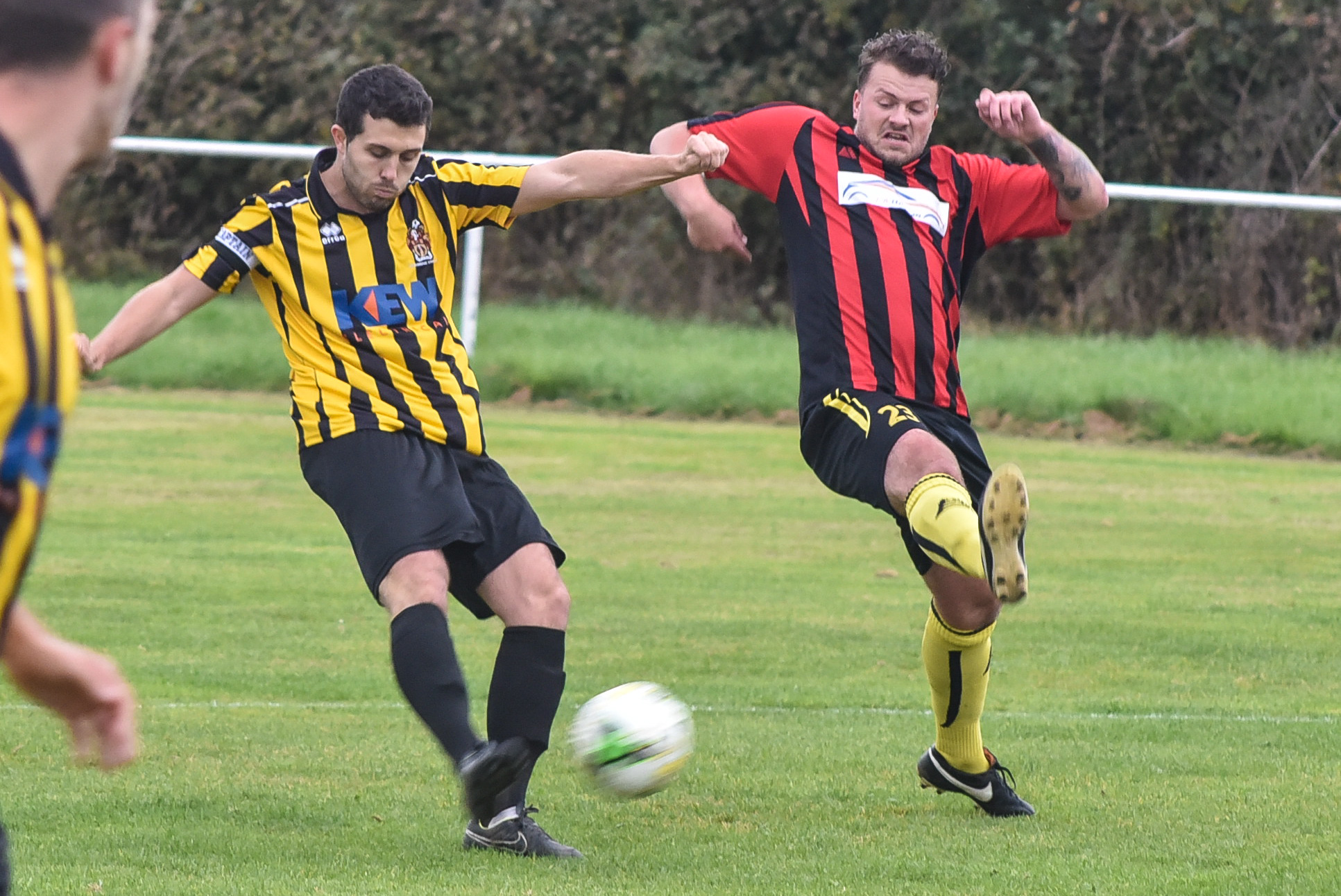 Beversbrook's Louis Wollen (red and black) closes down Trowbridge Town's Shaun Percival