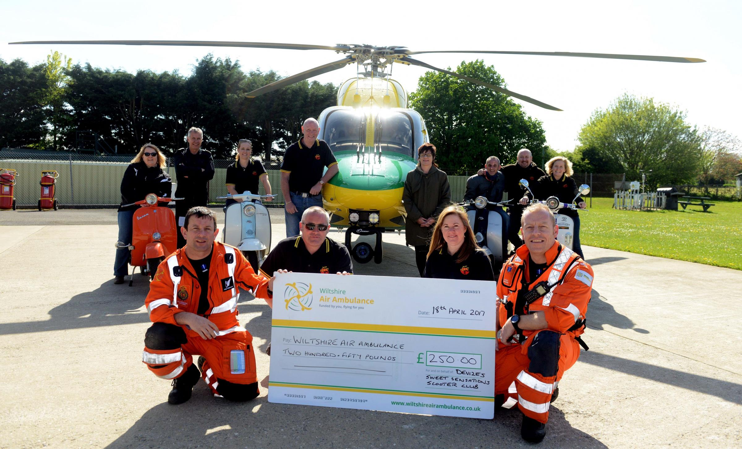Jay Webb and Sharon Todd present a cheque to Fred Thompson and Keith Mills of Wiltshire Air Ambulance watched by scooter club members. Picture by Siobhan Boyle