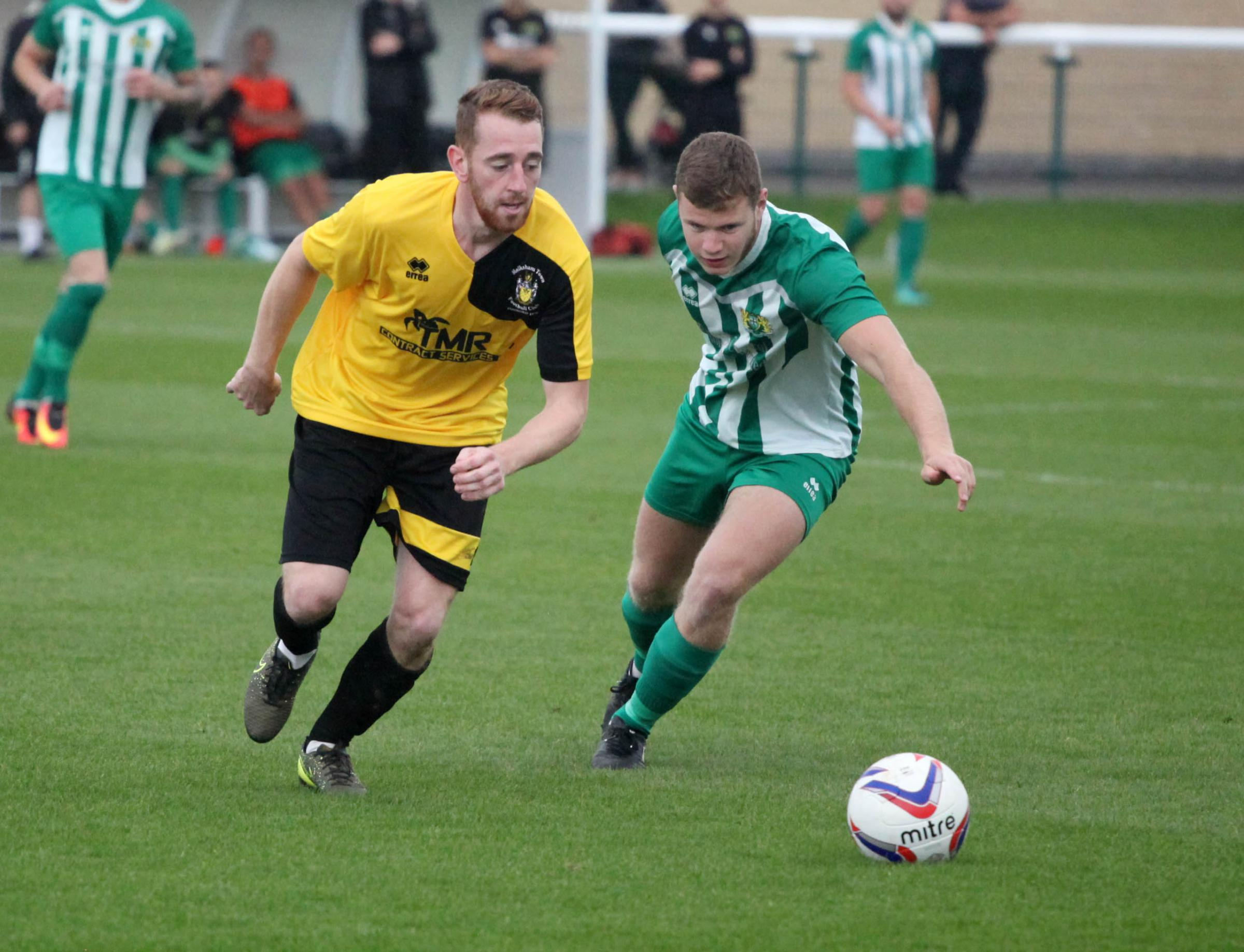 Melksham Town's Alex Grimshaw (yellow) takes on a Hengrove Athletic opponent on Saturday. PICTURE: VICKY SCIPIO