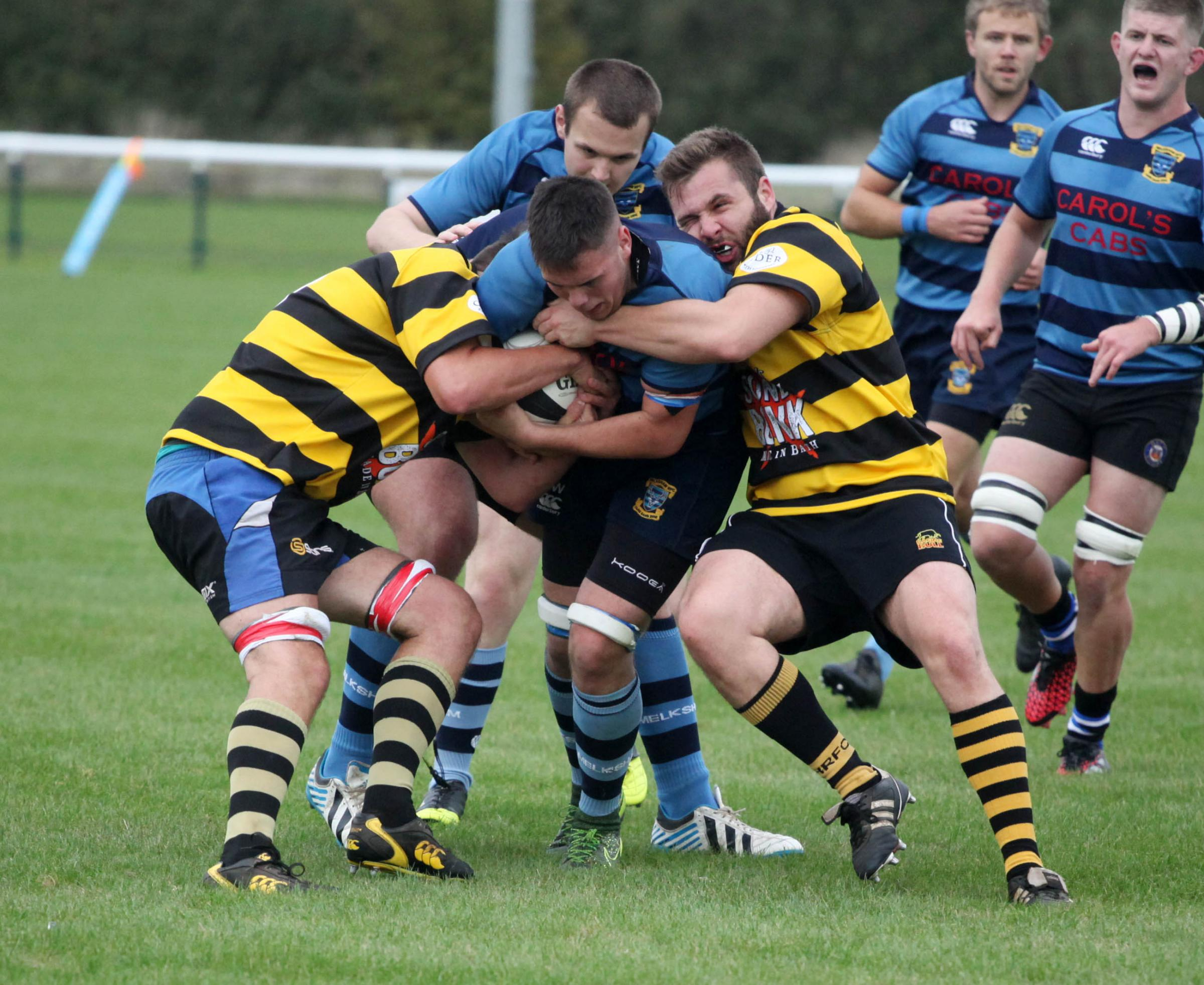 Melksham's Luke Wilkins (blue shirt) has his run halted by Combe Down's Bill Fairman
