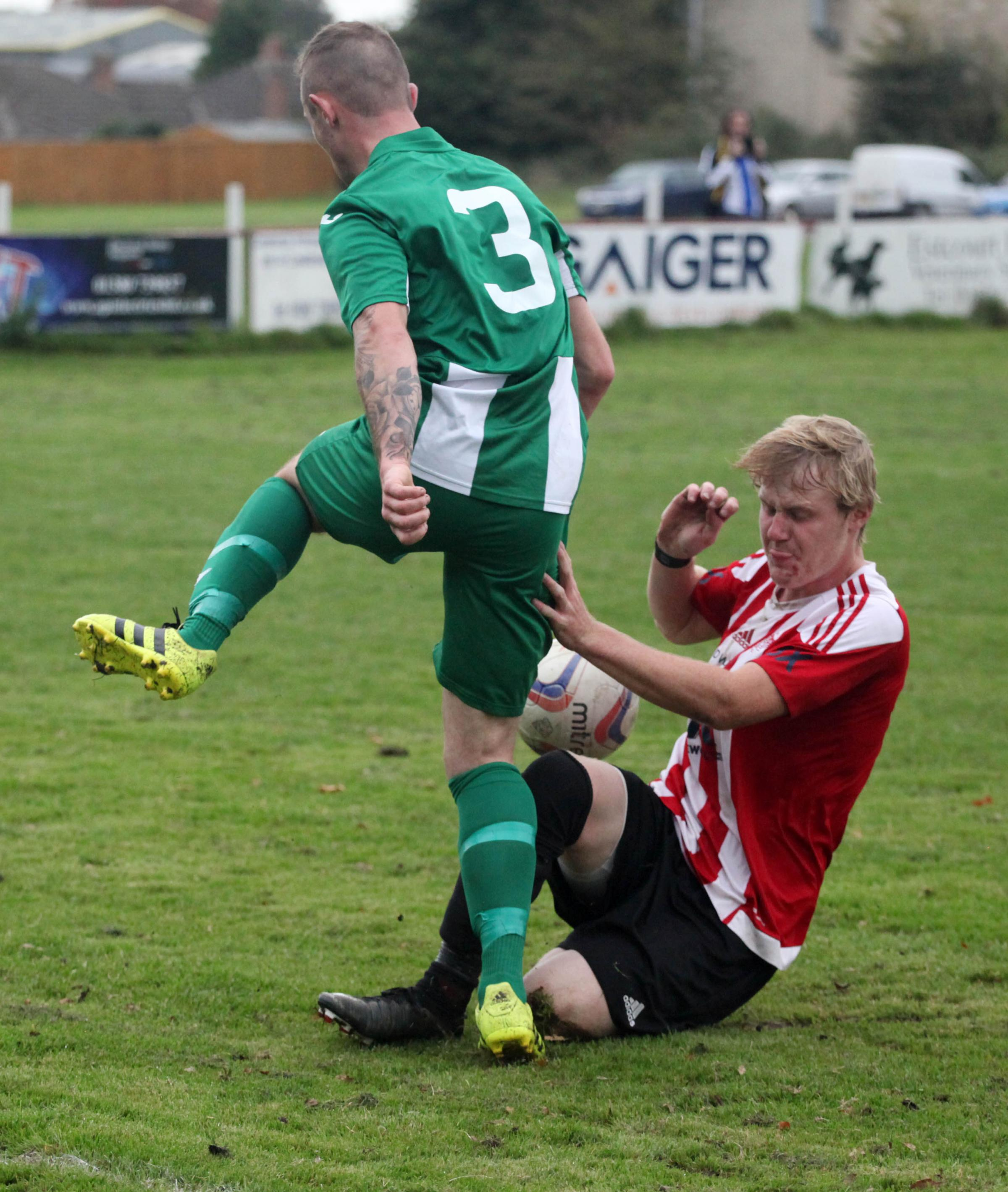 Devizes Town's Jamie Walters (red) gets in a tackle during his side's win over Wincanton Town on Saturday (Picture: VICKY SCIPIO)
