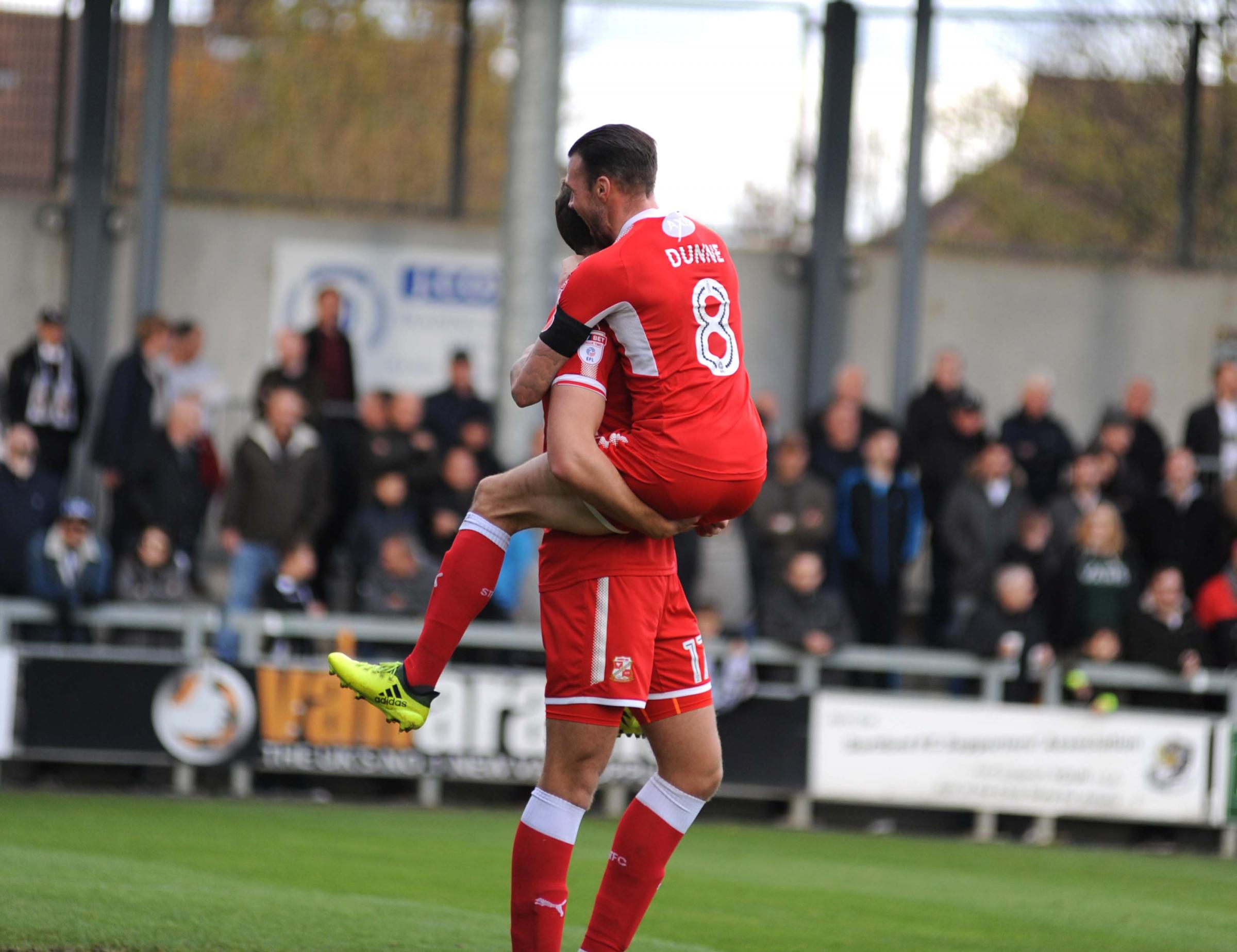 Swindon Town's James Dunne embraces Harry Smith after his goal at Dartford