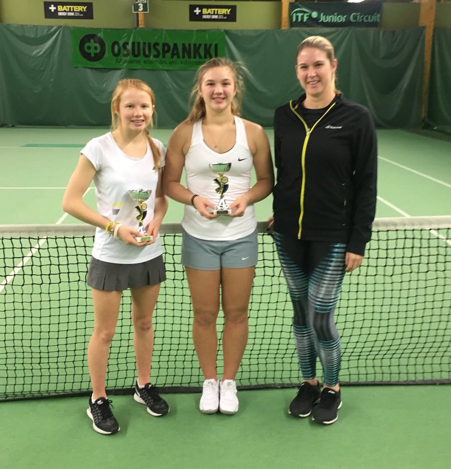 Amelia Bissett and Morgan Cross with coach Mel South after their girls' doubles title win in Finland.