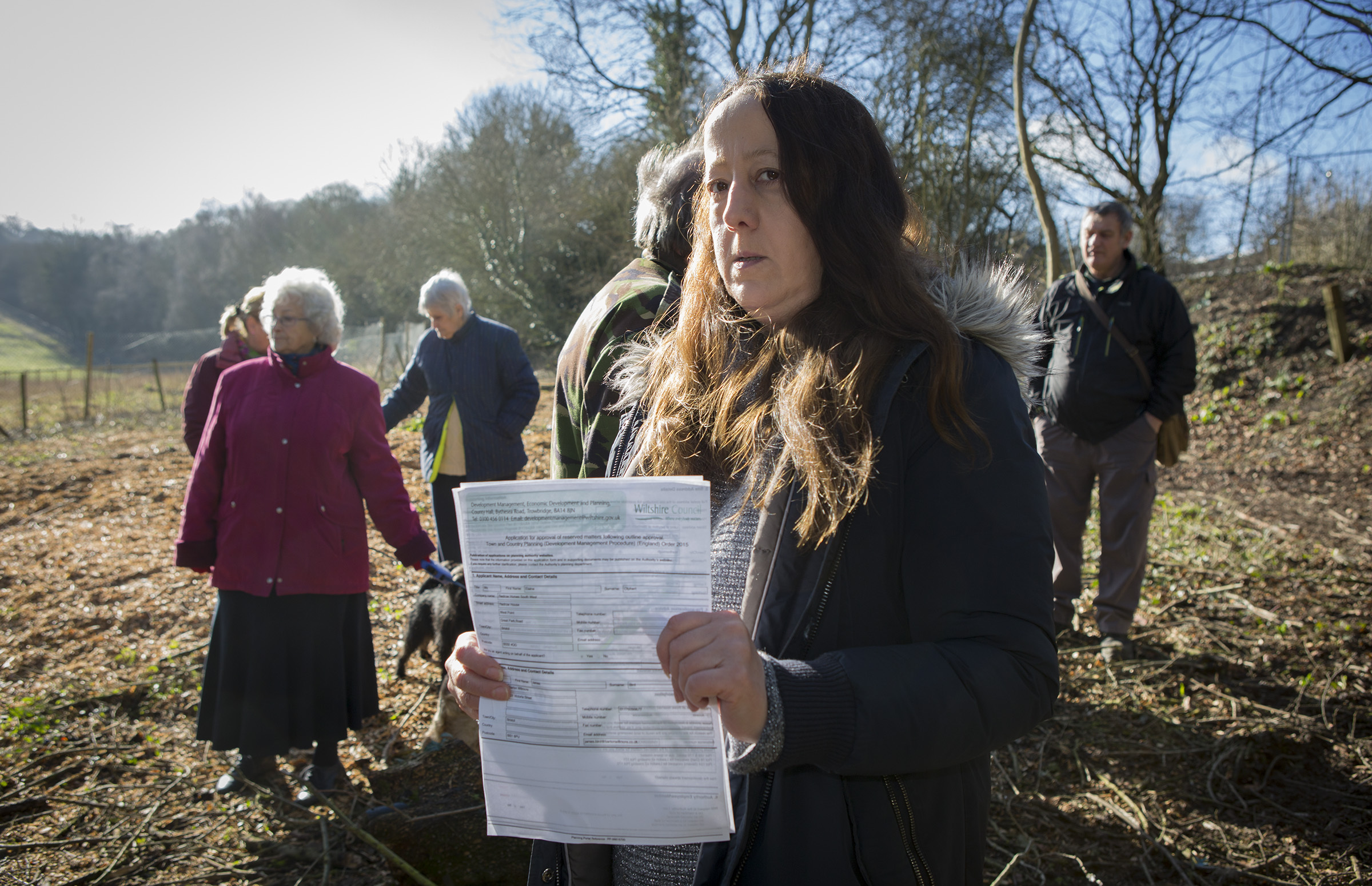 Sara Daw and other residents on the land where trees have been felled, with correspondence from Wiltshire Council                                                      Photo: Nicola Salt